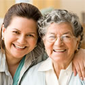 health care worker and senior embracing and smiling